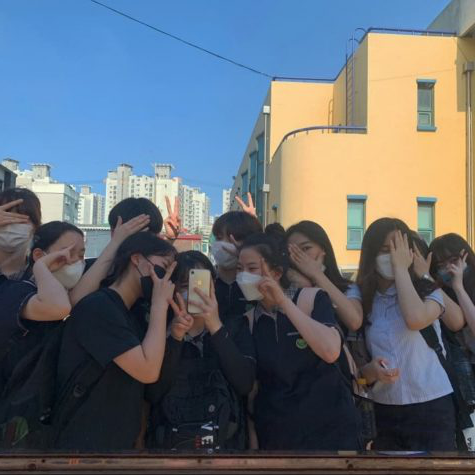 Korean students wear masks for a group photo. In Korea, there is much less of a negative perception around wearing masks to keep others safe.